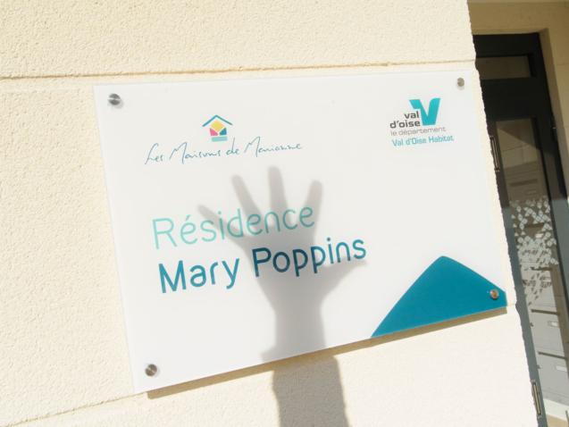 Photo de l'ombre d'une main devant la plaque d'accueil de la résidence de Vauréal pour l'article sur les oeuvres créées entre l'école Talentiel et la résidence